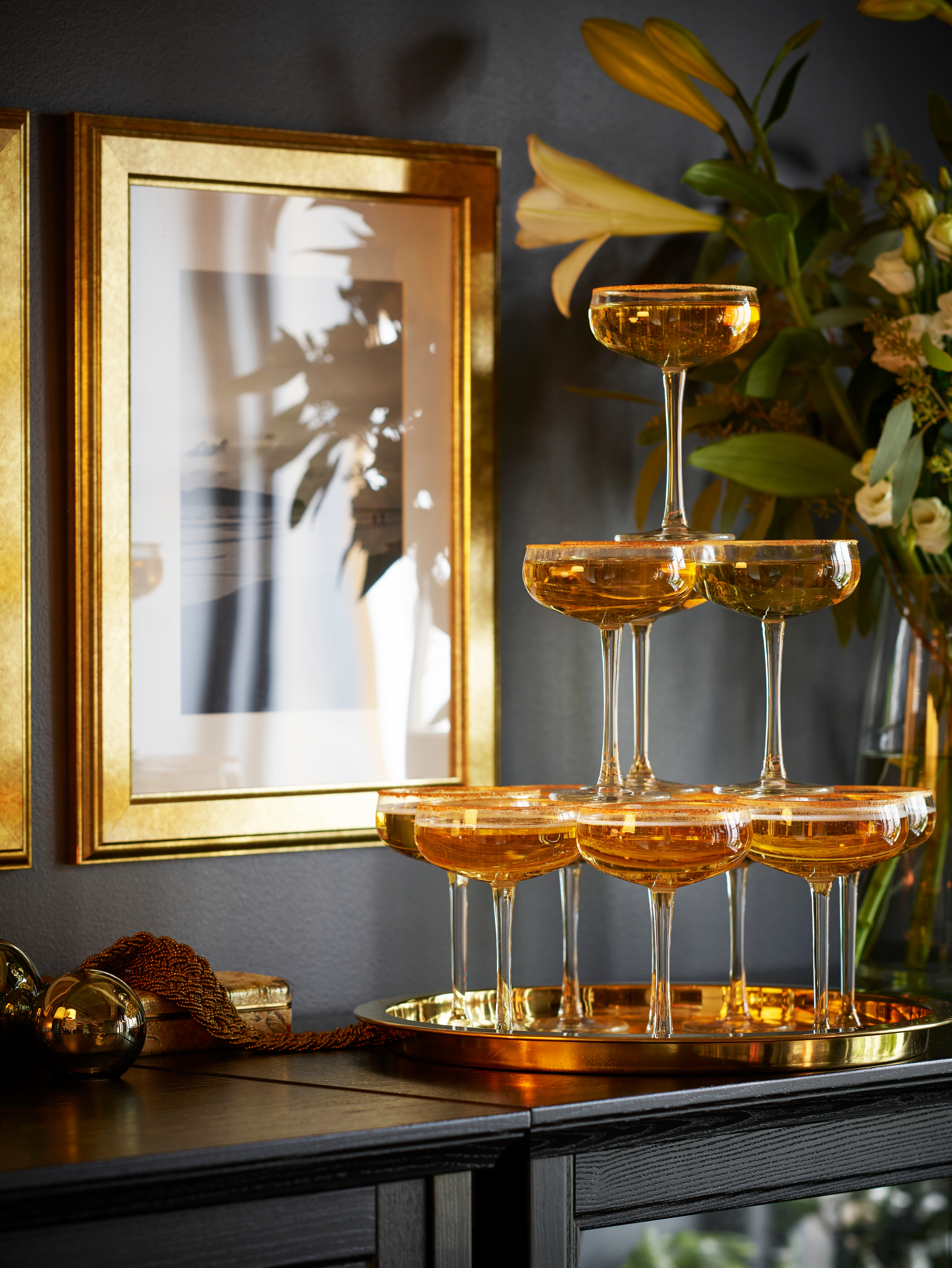 A festive towering pyramid of clear glass STORHET champagne coupes with gold liquid stand on brassy tray on top of a cabinet.