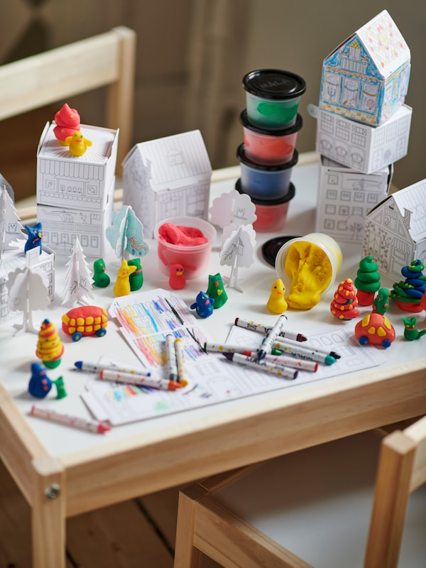 A table with paper and crayons, paints, and other art supplies.