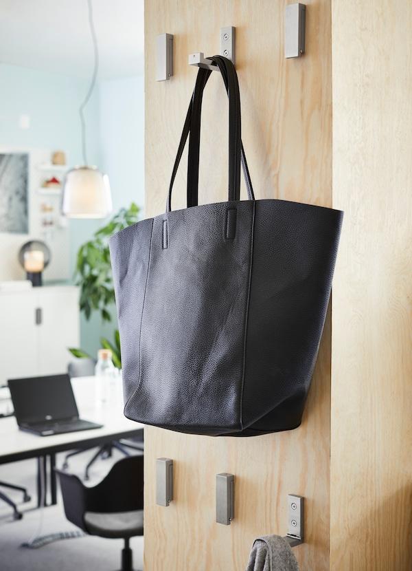 Ganci pieghevoli in alluminio BJÄRNUM fissati a una parete divisoria; una borsa nera appesa a uno dei ganci.