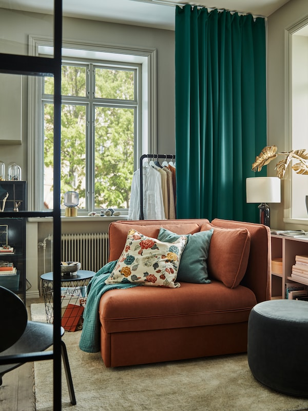 Dark turquoise MAJGULL block-out curtains hang in a corner behind a VALLENTUNA sofa-bed module with backrests.
