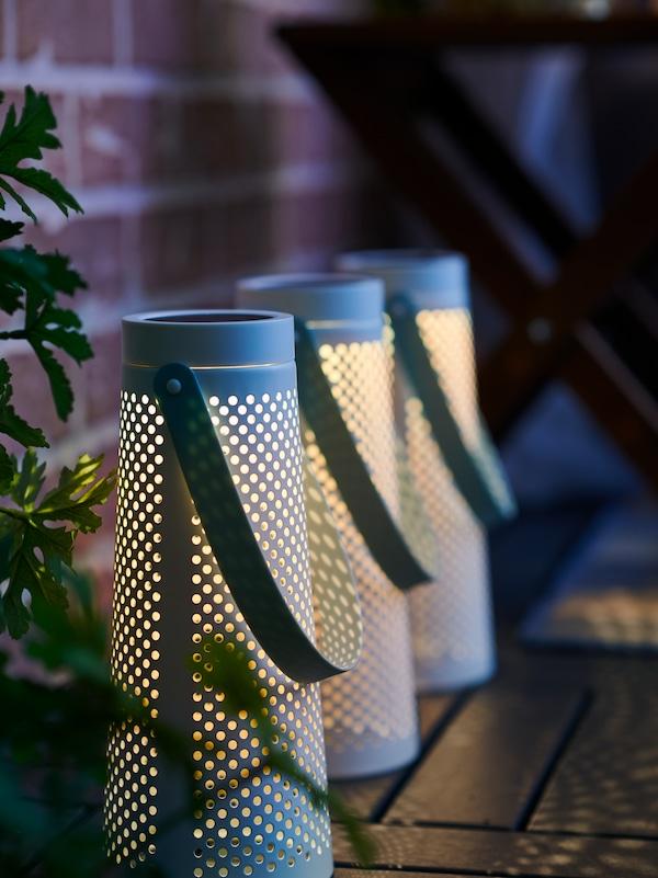 Zewnętrzne lampy LED SOLVINDEN rzucające światło na drewnianą podłogę balkonu po zmierzchu.