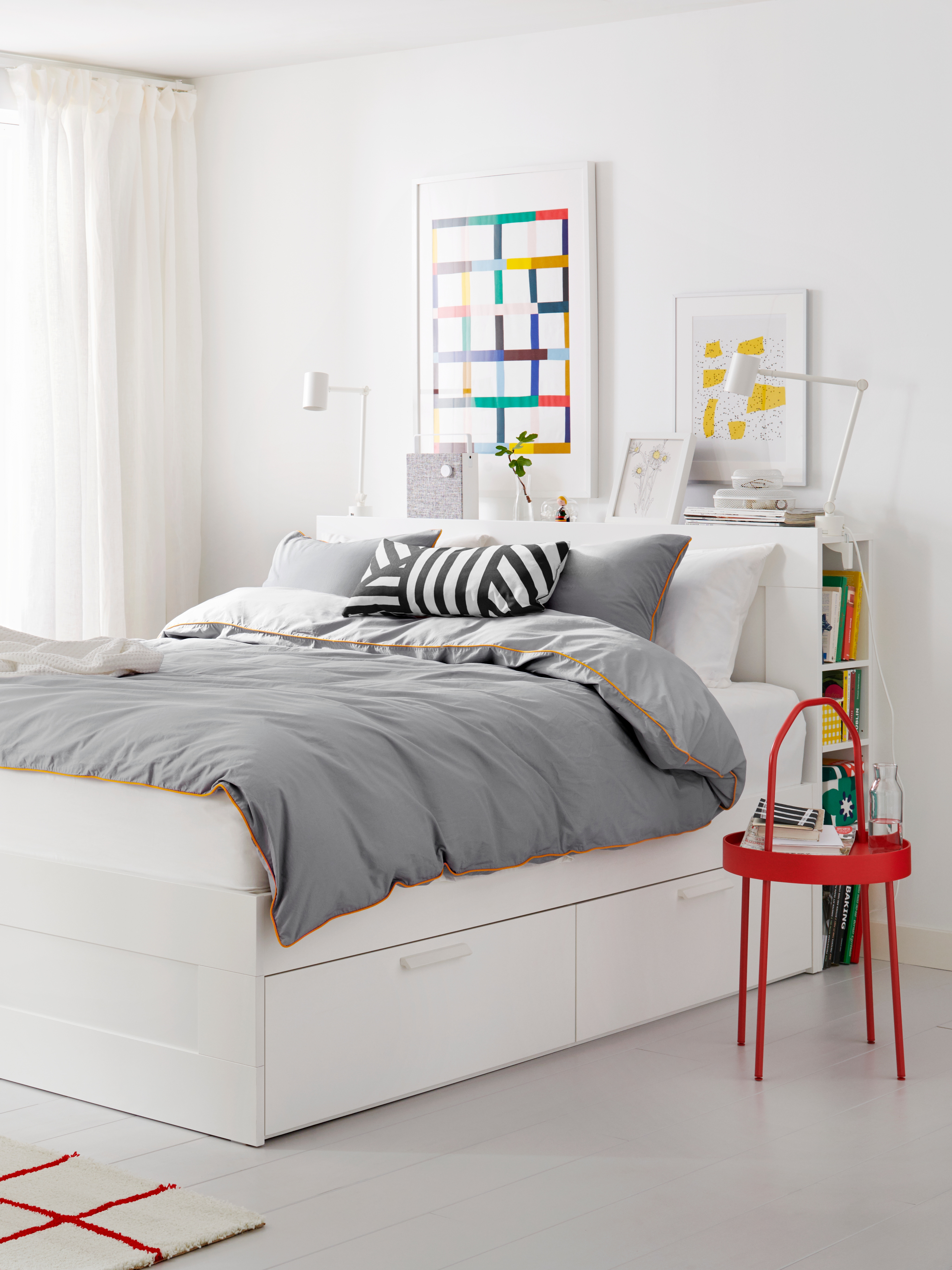 BRIMNES bed frame with gray/yellow bedding, a Bluetooth speaker on the shelf and a red bedside table in a bright bedroom.