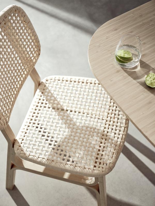 Egy VOXLÖV bambusz széket látunk, amely egy VOXLÖV bambusz asztal mellett áll. Az asztalon egy szelet lime-mal díszített vizespoharat látunk.