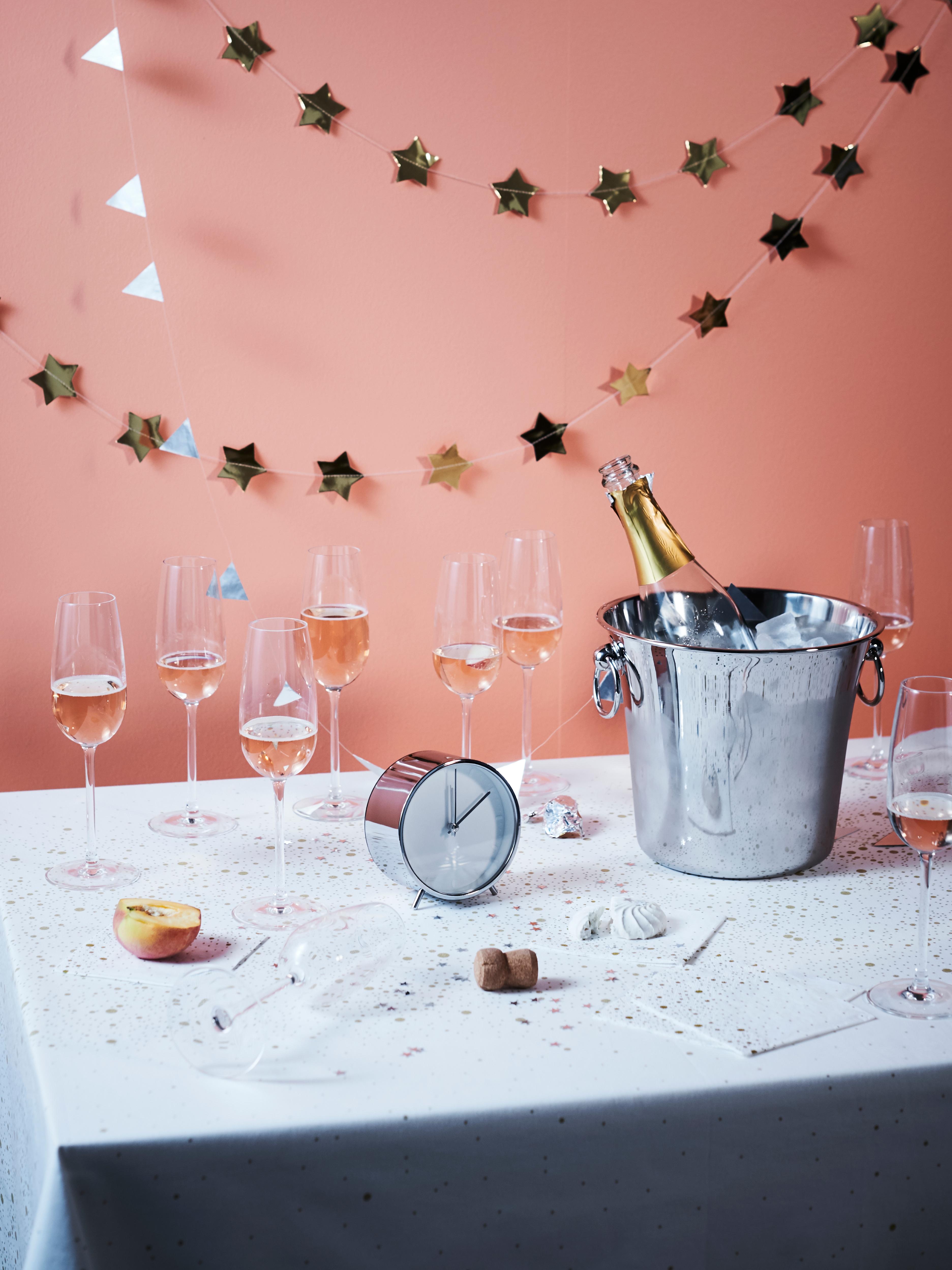STORSINT čaše sa šampanjcem na stolu punom konfeta s bocom u posudi za led, dekorativnim lancem sa zlatnim zvijezdama i satom.
