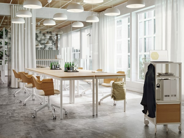 Swivel chairs around conference tables with wooden tabletops in an open setting. White lamps hang from the ceiling above.