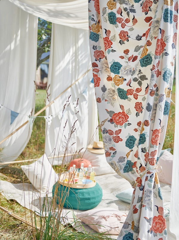 Unbleached BOMULL fabric and patterned TROLLMALL fabric are draped across poles to create a cosy bohemian tent.