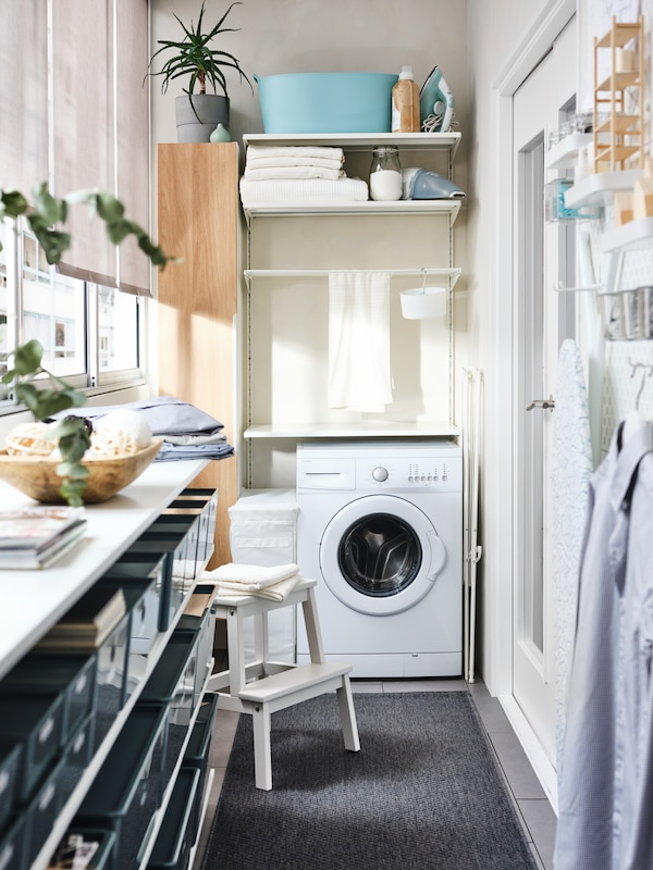 A white BOAXEL storage system with a washing machine and folded towels, beside a tall white/oak ENHET cabinet on a balcony.