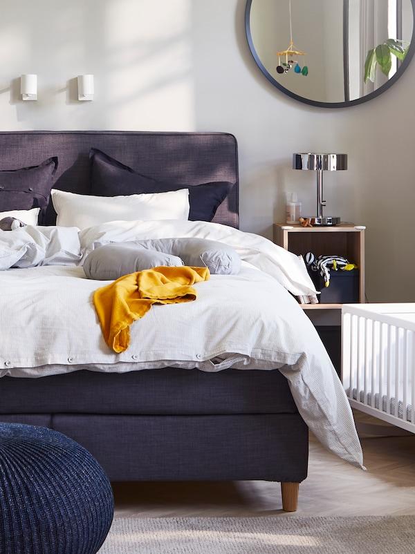 Dormitorio con un diván cama DUNVIK en gris oscuro, fundas nórdica y de almohada en gris/de rayas, dos lámparas de lectura blancas y una cuna.