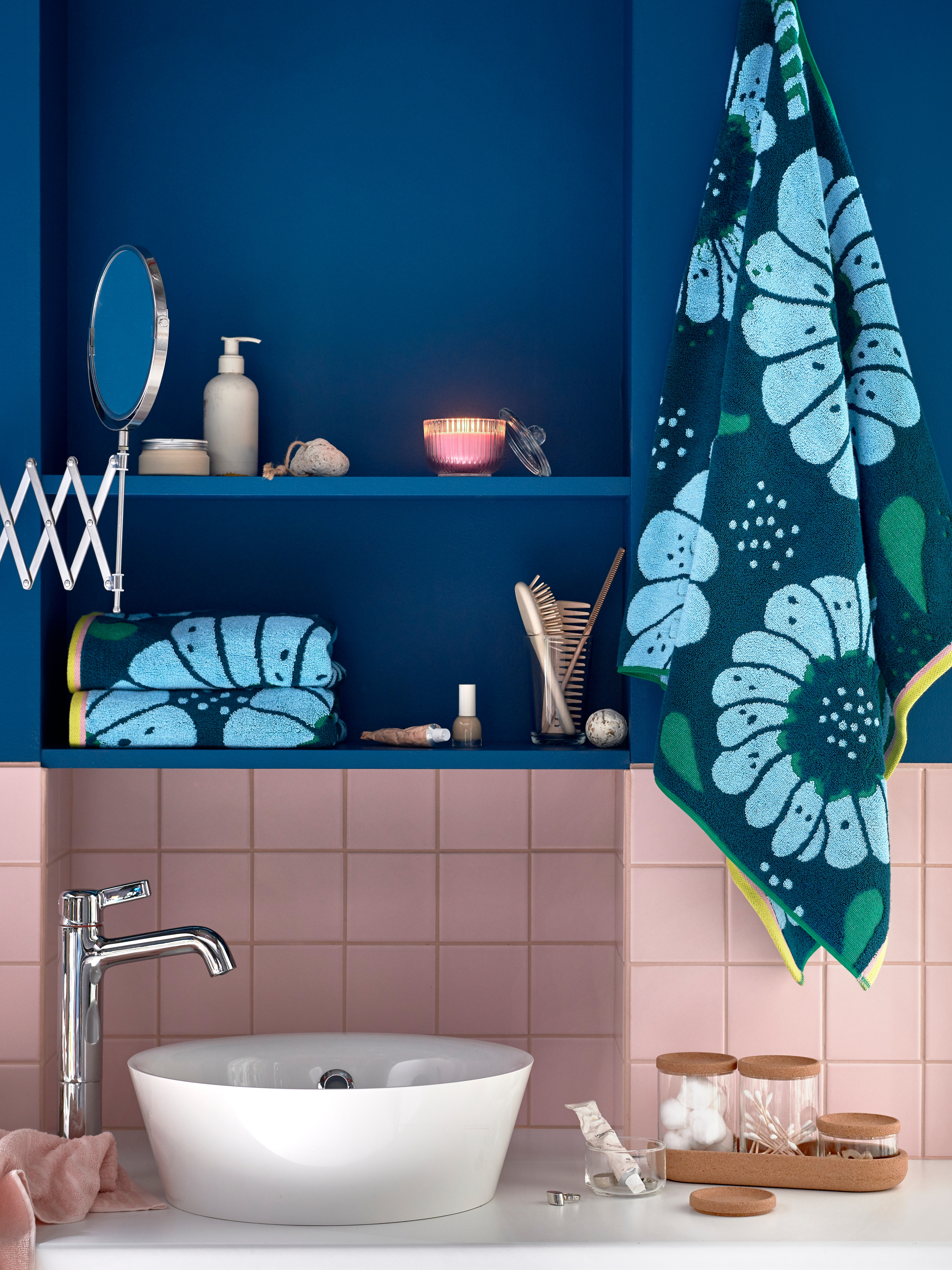 KATTEVIK countertop wash basin sitting atop a white counter below a blue painted wall, and with blue floral print towels.