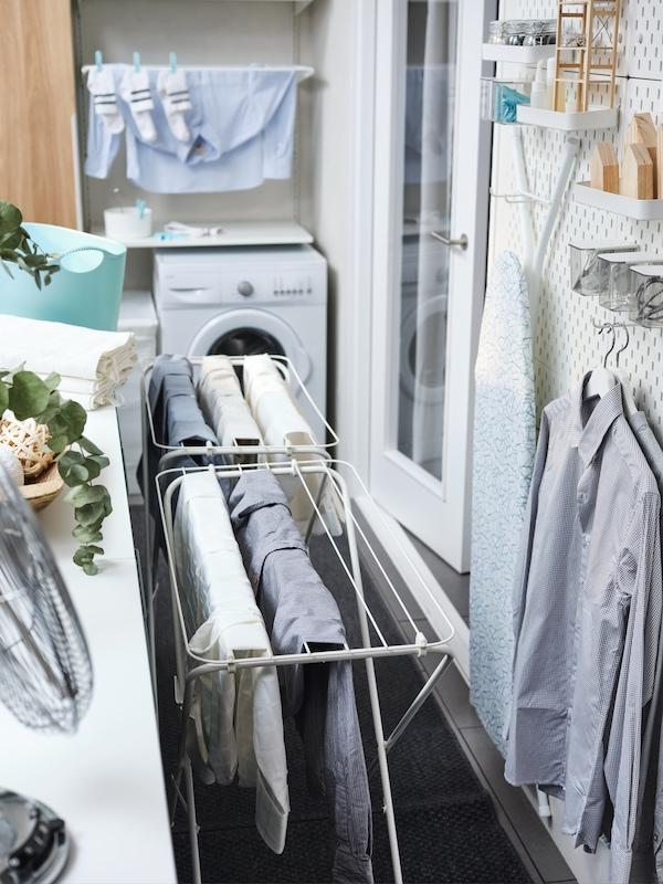 Dois estendais JÄLL em branco com roupa, junto de prateleiras em branco e arrumação de parede com camisas em cabides e tábua de engomar.