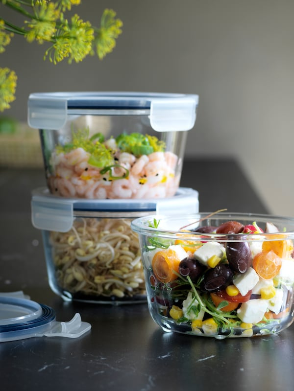 Tre runde IKEA 365+ madopbevaringsboksei glas med forskelligt indhold står på et køkkenbord.