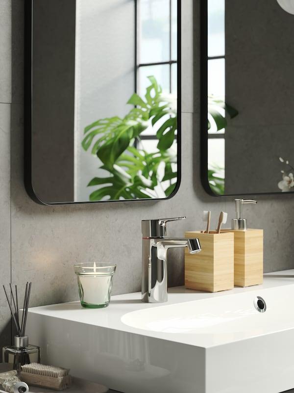 Sur un lavabo blanc, un distributeur de savon DRAGAN en bambou et un porte-brosses à dent, une bougie parfumée VÄLDOFT dans un verre vert clair.