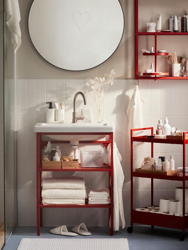 Bad med rødoransje baderomsmøbler, blant annet et veggskap, en åpen servantstamme og et rundt speil.