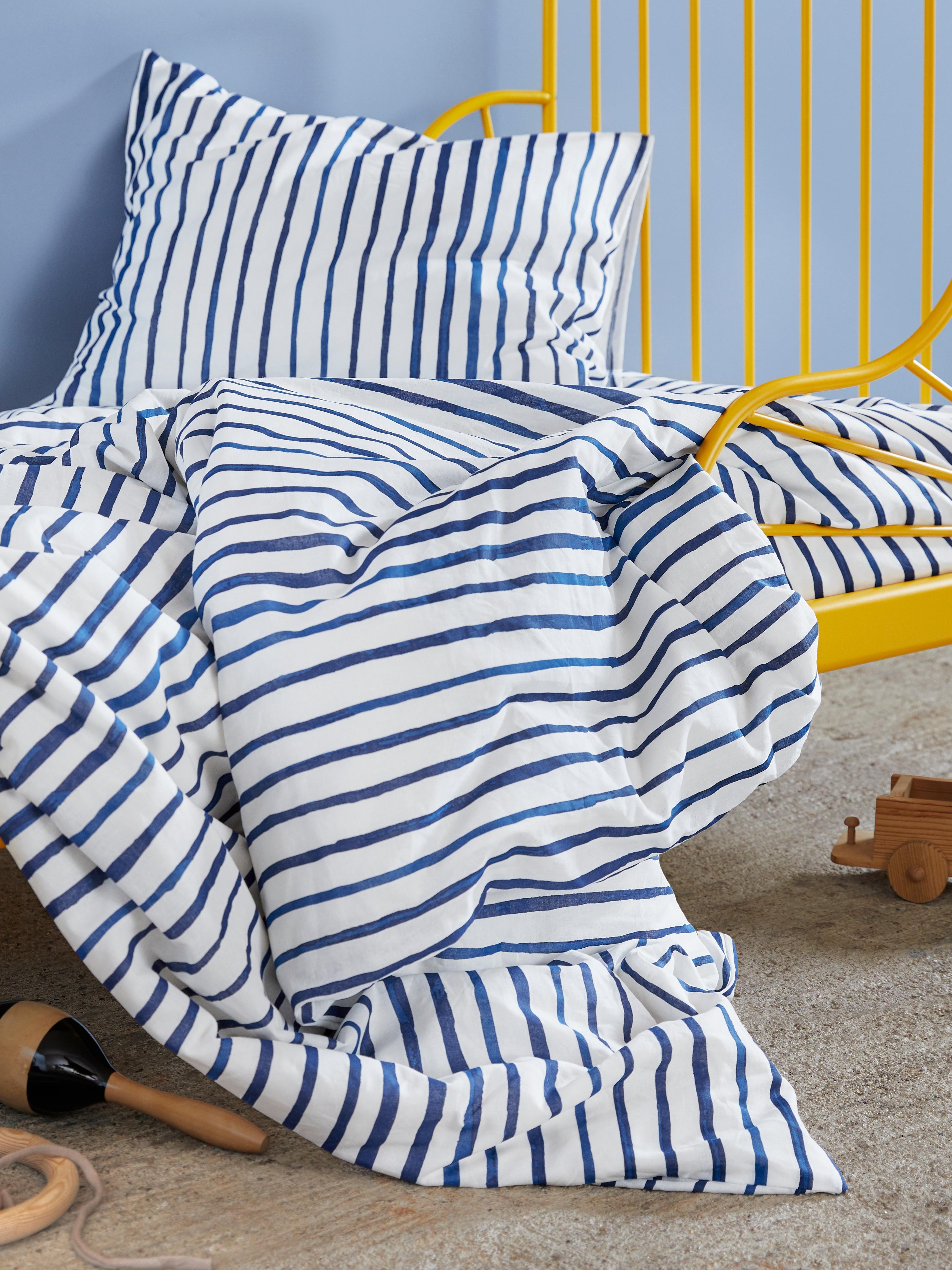 Nekoliko igračaka na tepihu ispod okvira dečjeg kreveta na kom se nalaze prugasta plavo-bela SÅNGLÄRKA jorganska navlaka i jastučnica.