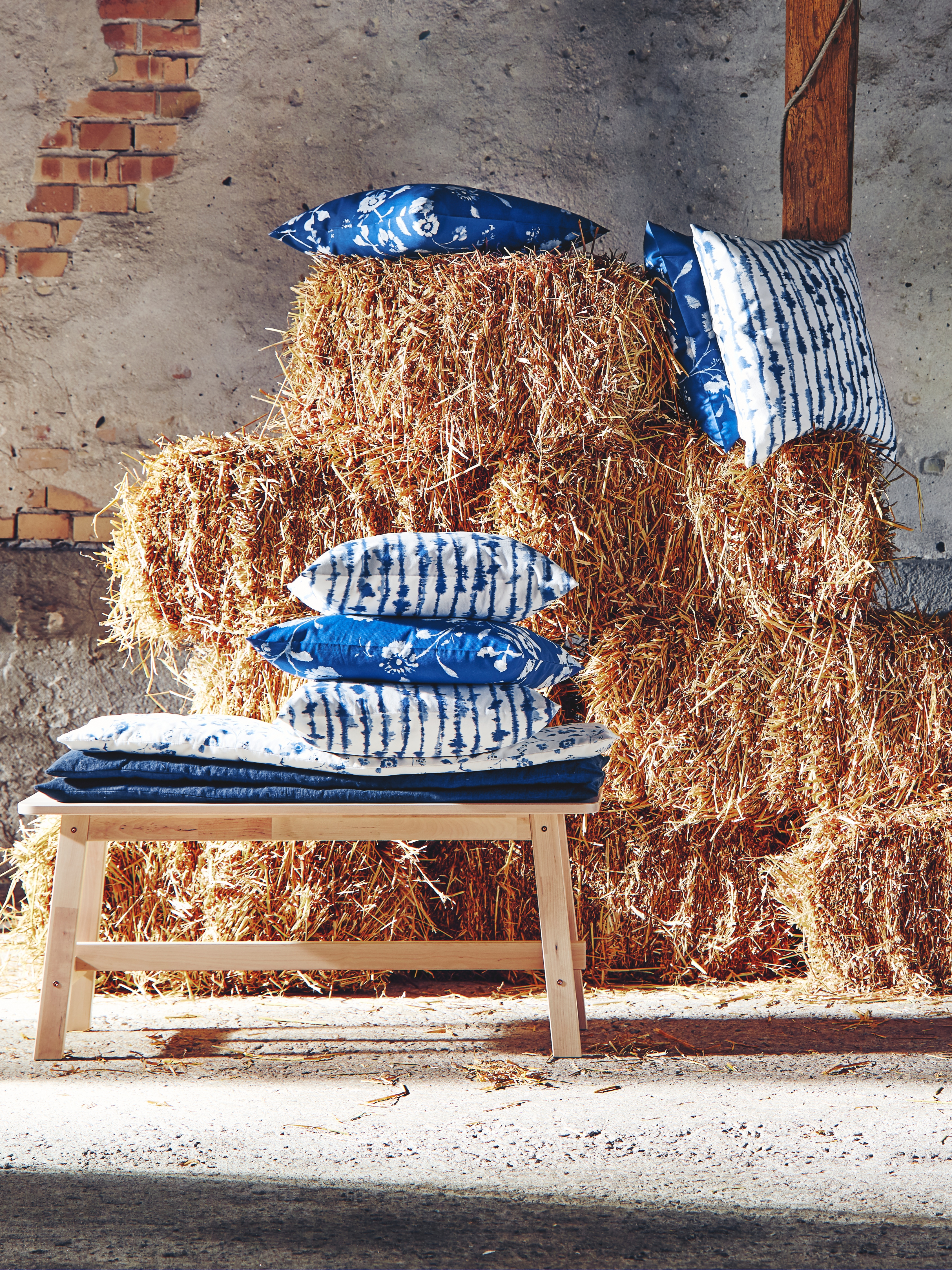 STRIMSPORRE blue and white cotton cushion-covers on top of a haystack and a bench in birch.