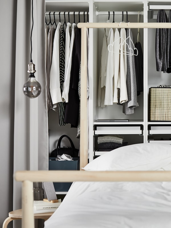White PAX wardrobe combination holding different clothing items and storage boxes set in a contemporary airy bedroom.