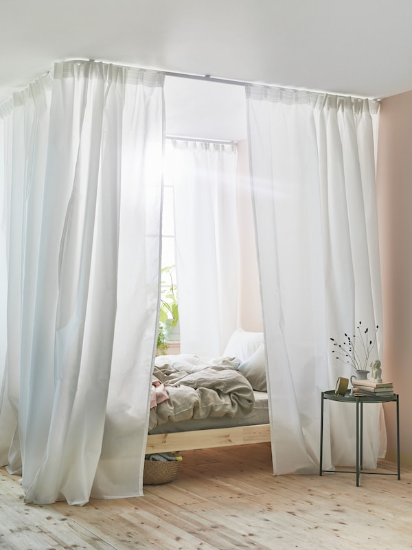 A wooden bed with a canopy of white curtains around it made using VIDGA curtain track rails mounted to the ceiling.
