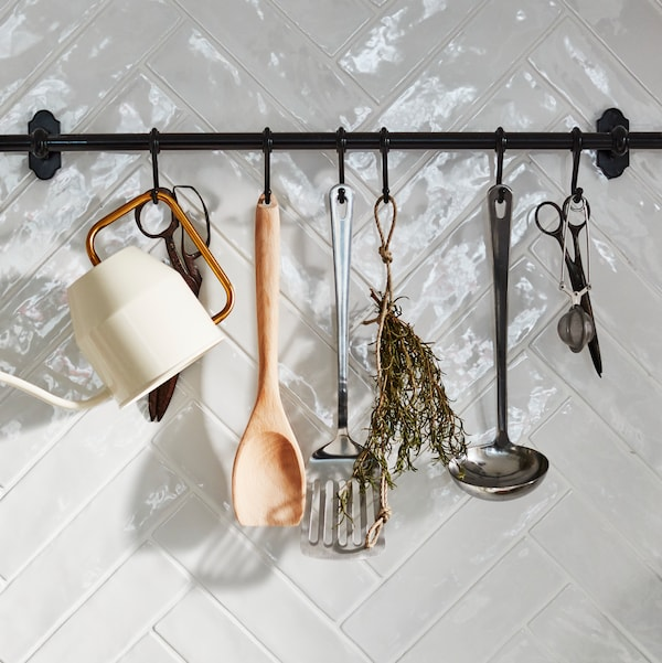 A black rail on a white-tiled wall with kitchen tools, scissors, a watering can and a dried herb hanging from hooks.