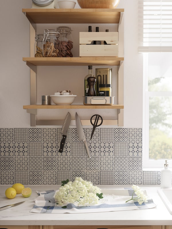A wall-mounted IKEA KUNGSFORS ash veneer suspension rail with shelves and a magnetic knife rack, patterned tiles below.