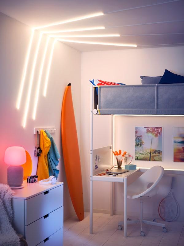 Pokój z ramą łóżka na antresoli VITVAL, deska surfingowa, listwy oświetleniowe LED MYRVARV na ścianie oraz lampa stołowa z głośnikiem Wi-Fi.