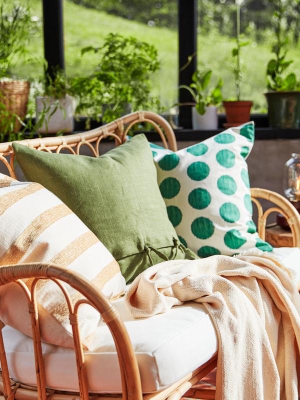 Un coxín KNIPPARV de raias, un coxín nunha funda AINA verde e un terceiro coxín nunha funda ÅSATILDA de lunares sobre un sofá MASTHOLMEN.