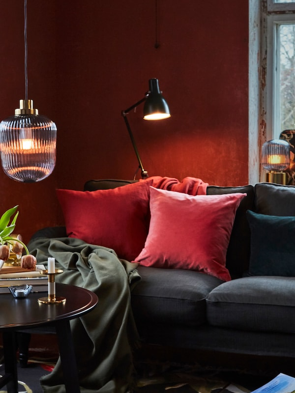 Cushions and a throw lie on top of a STOCKSUND sofa that is under an ARÖD floor/reading lamp and beside a KRAGSTA table.