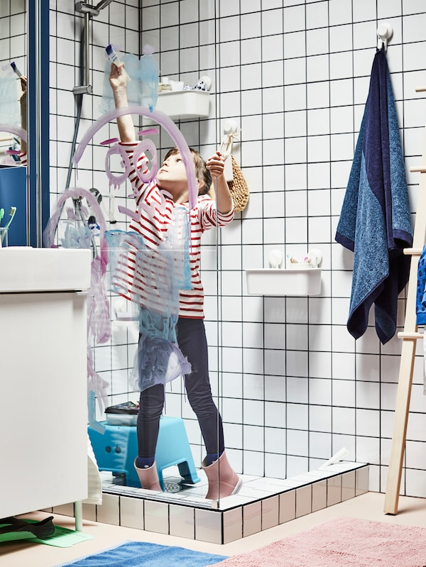 A child paints on the screen of a white-tiled shower, a blue towel hangs from a TISKEN suction hook on the wall behind.