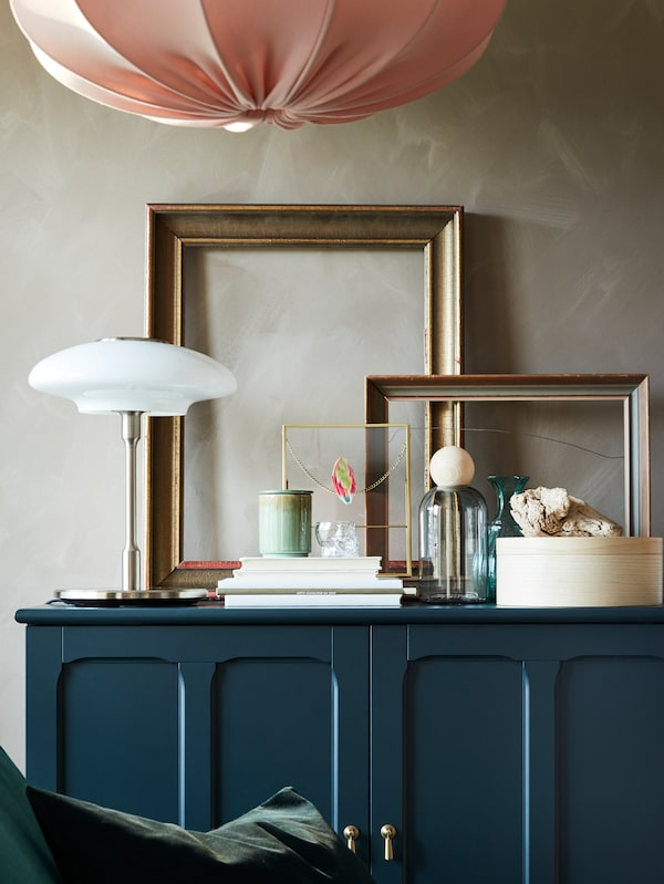 Golden frames, books, decorative items and a table lamp in nickel-plated/opal white glass stand on a blue-green cabinet.