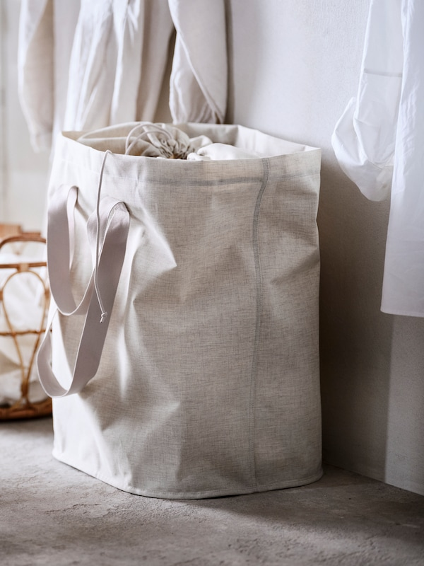 A beige PURRPINGLA laundry bag containing dirty laundry stands on the floor against a white wall.