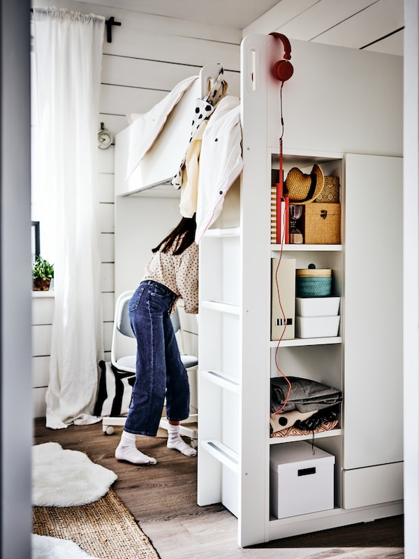 A girl standing by an ÖRFJÄLL chair at her desk under a white loft bed. Storage boxes are on shelves in the bed frame.
