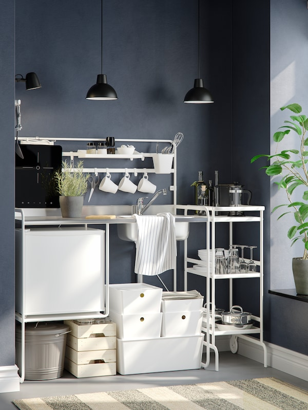 A white SUNNERSTA mini-kitchen with two pendant lamps against a dark gray wall, next to a window with a flower pot.