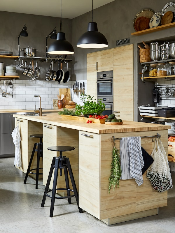 A kitchen with grey walls and white tiles and a large ASKERSUND kitchen island. Pots and pans hang from KUNGSFORS shelves.