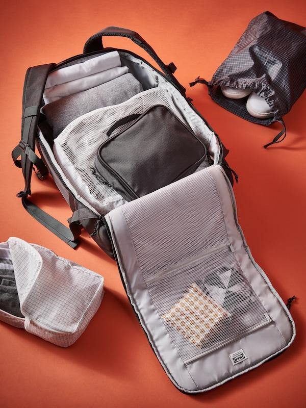 Un sac à dos VÄRLDENS gris foncé ouvert et rempli de sacs RENSARE sur une surface orange.