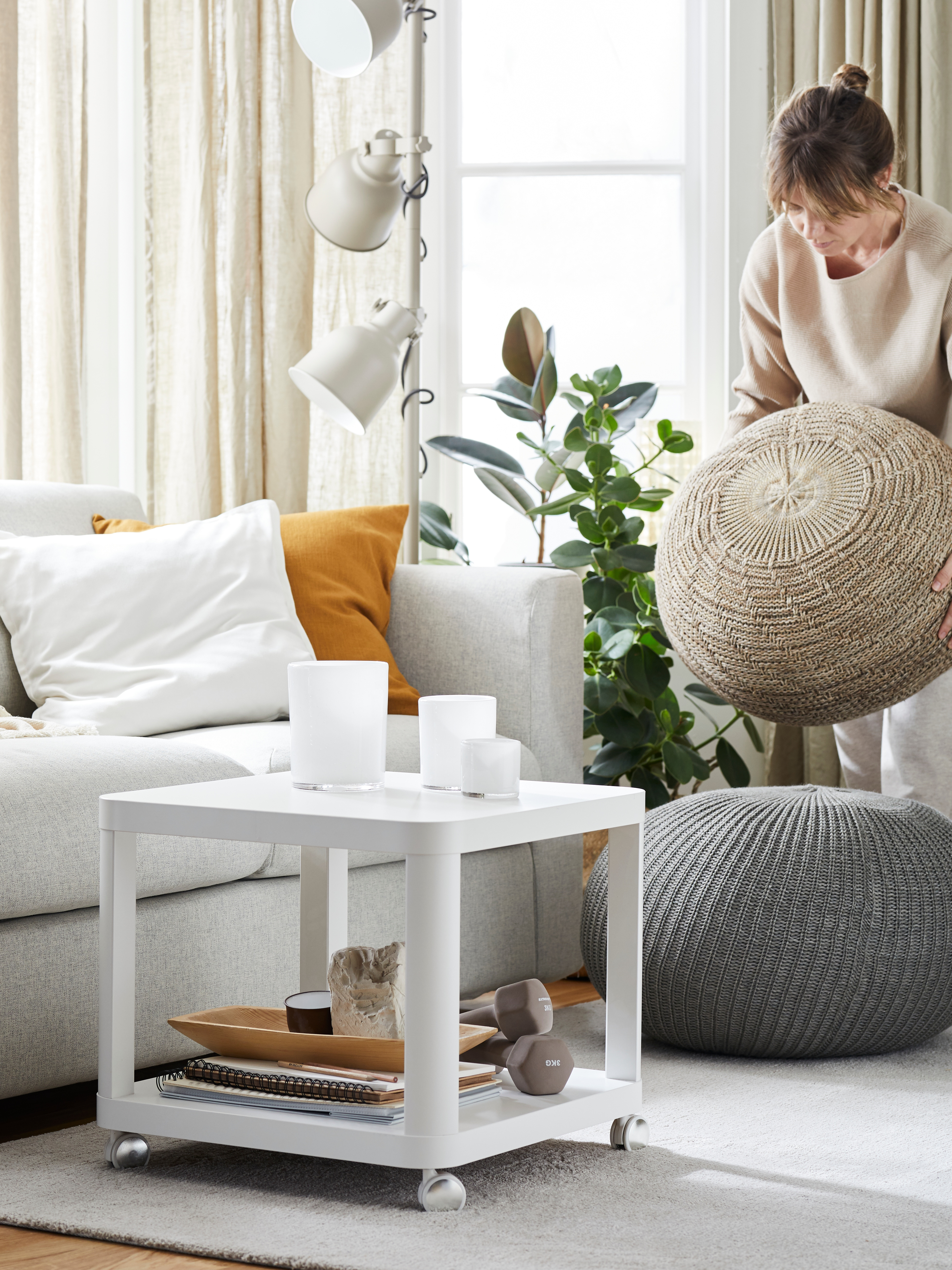 A white TINGBY side table on castors holds candles and dumbbells by a sofa. A person is stacking woven pouffes nearby.
