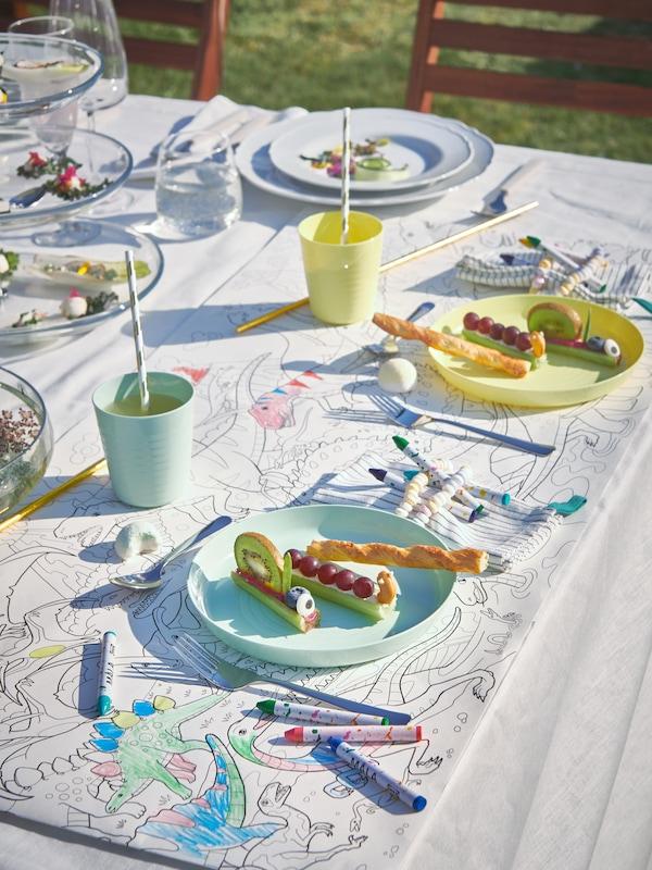 Dous servizos para nenos con lapis de cera MÅLA e un rolo para colorear JÄTTELIK como tapetes nunha festa no exterior.
