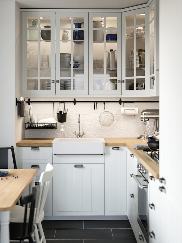 Cociña STENSUND branca de estilo tradicional con portas de cristal, un vertedoiro HAVSEN branco e un mesado SÄLJAN de efecto de carballo.
