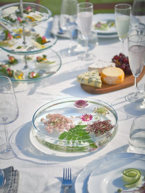 As flores flotan nun cunco BERÄKNA cheo de auga sobre unha mesa con vasos SVALKA e bandexas para servir KVITTERA con alturas.