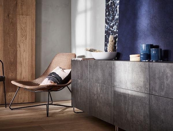 Un televisor en una pared encima de un mueble de TV BESTÅ blanco. Hay armarios BESTÅ con puertas LAPPVIKEN blancas y de vidrio en la pared de encima.
