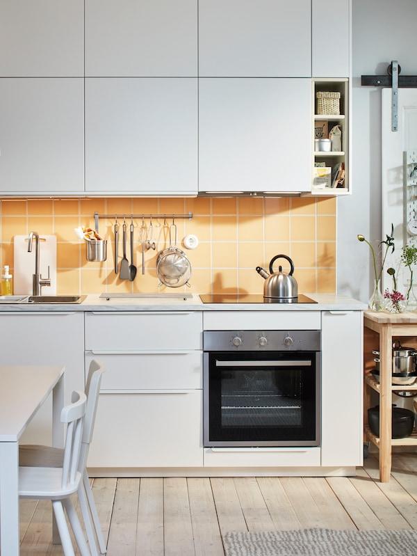 Una pequeña cocina blanca con armarios bajos y de pared en color blanco, azulejos amarillos y un horno.