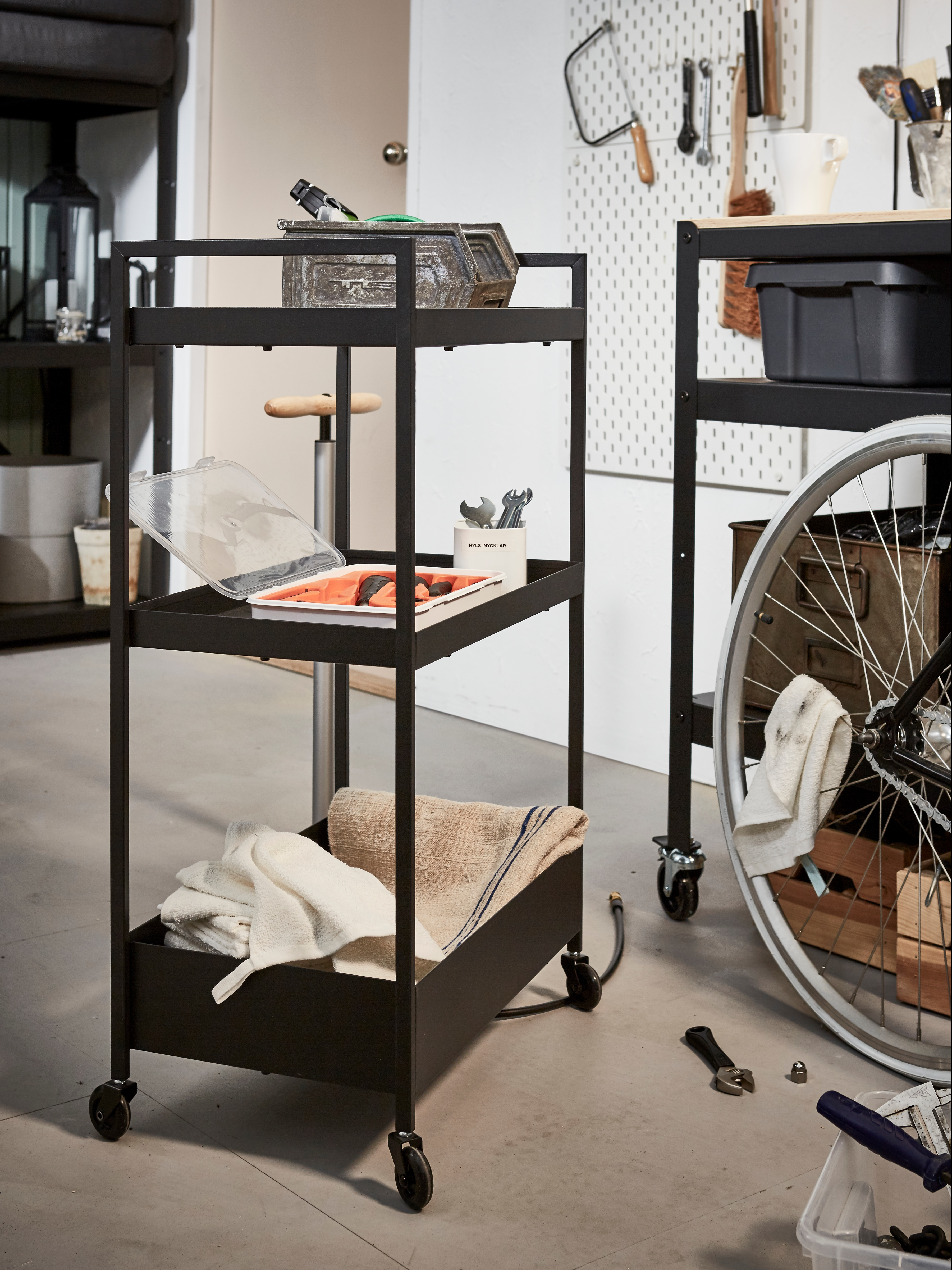 A wheeled, black-coated steel NISSAFORS trolley that has three shelves filled with tools on a garage floor by a bicycle.