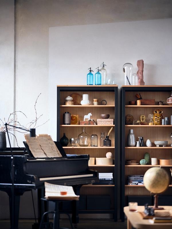 Un armario HEMNES lleno de objetos de cerámica, libros, cajas de almacenaje y otros objetos.