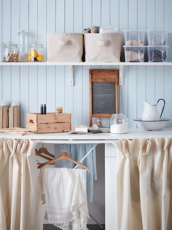 Une salle de lavage bleue avec beaucoup d'espace de rangement et des rideaux pour dissimuler la laveuse et la sécheuse.