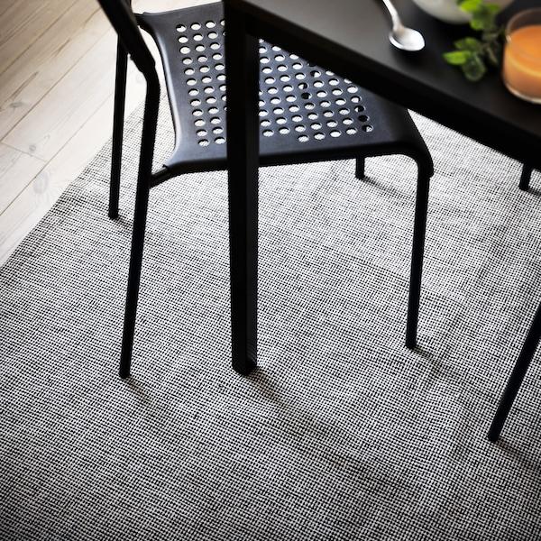 Nogle sorte ADDE stole står ved et spisebord på et gråt/hvidt fladvævet TIPHEDE tæppe på et trægulv.