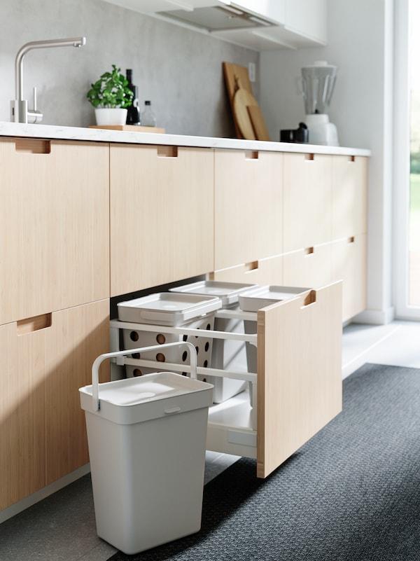 Køkkenskuffefronter af bambus, lysegrå affaldssorteringsspande, et sort tæppe og et stålfarvet blandingsbatteri.