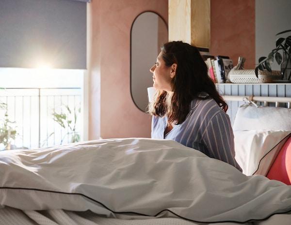 En kvinna sitter nyvaken i ett ljust soligt sovrum med KUNGSBLOMNMA påslakan och kuddfodral i sängen.