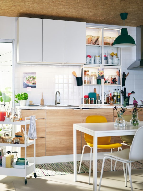 A light kitchen with ENHET cabinets, a white MELLTORP table, different-colour LEIFARNE chairs, and a white NISSAFORS trolley.