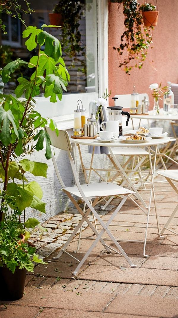 Uma mesa de exterior com muitas cadeiras, pratos e outros artigos e candeeiros suspensos debaixo de um grande guarda-sol.