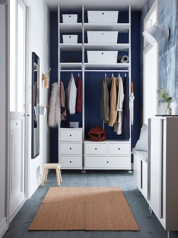A narrow blue and white hallway with ELVARLI storage at one end, made up of drawer units, a hanging rail and shelving.