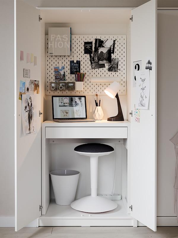 Un escritorio MICKE branco, un soporte de pé NILSERIK e un taboleiro de pinzas SKÅDIS dentro dun armario de dúas portas KLEPPSTAD branco.