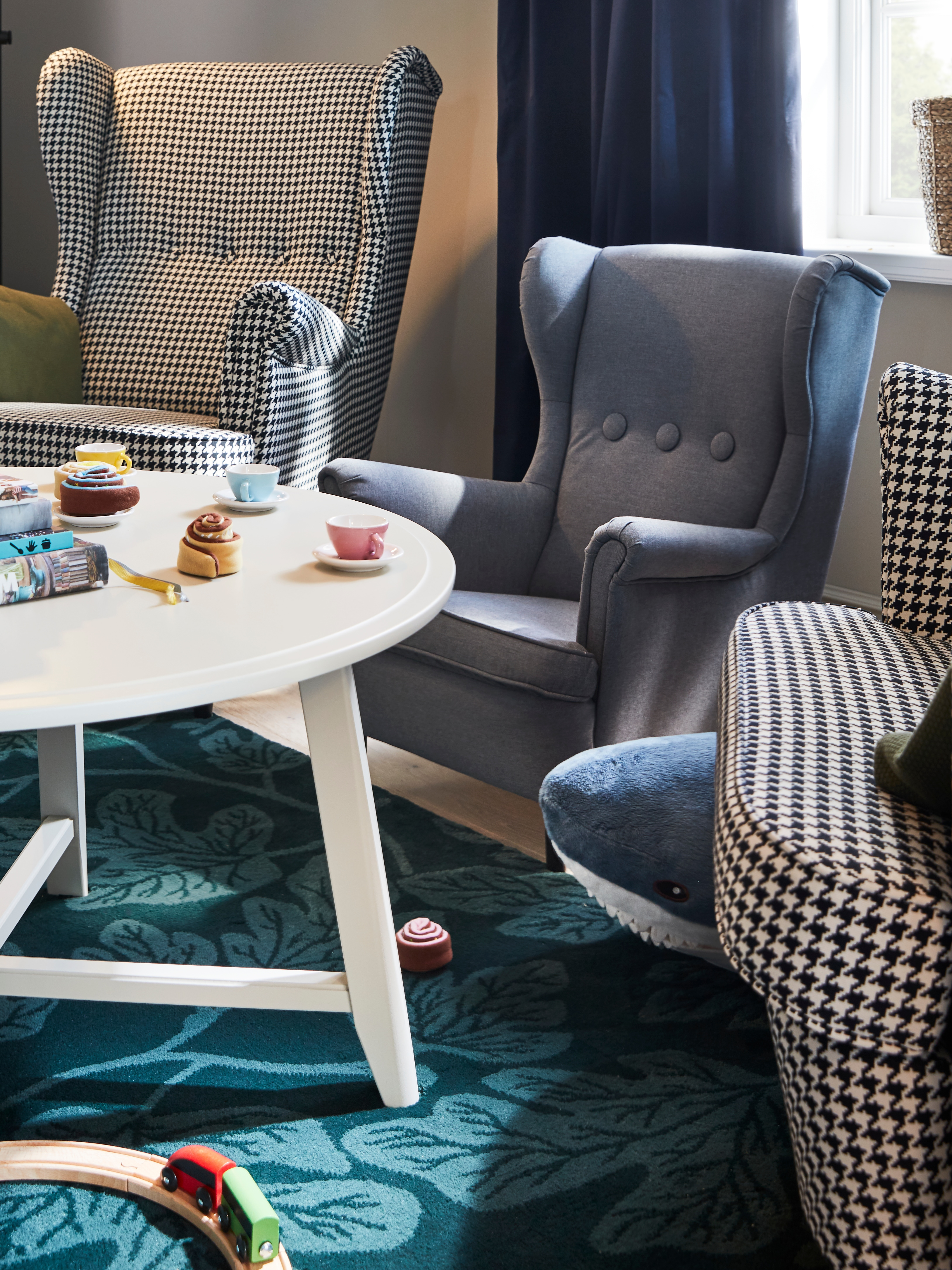Two wing chairs and a miniature children's armchair are by a light beige round KRAGSTA table with pretend tea and cake on it.